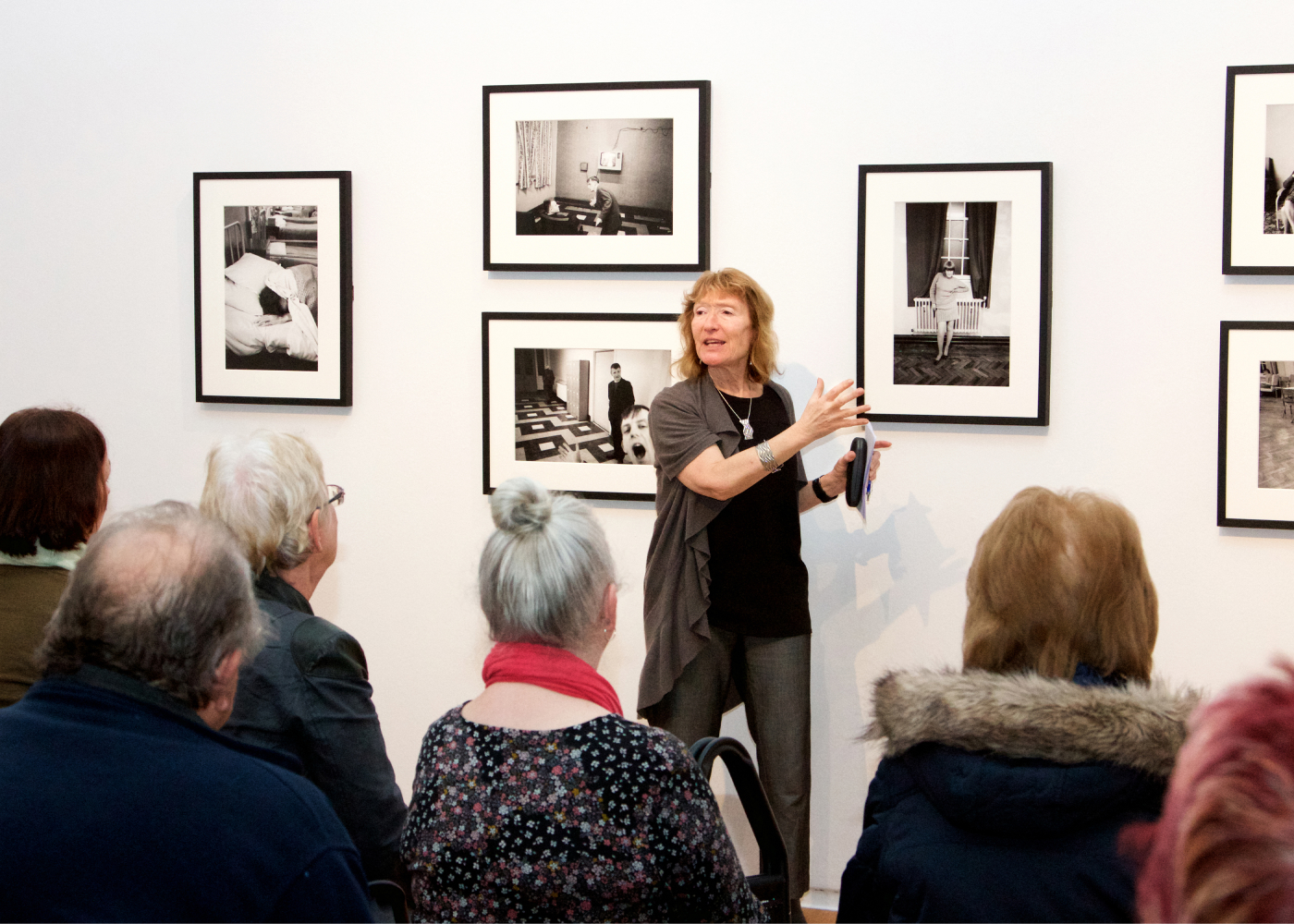 Anne Hornsby audio describing photographs by Martin Parr at an exhibition at Manchester Art Gallery to a group from Henshaws