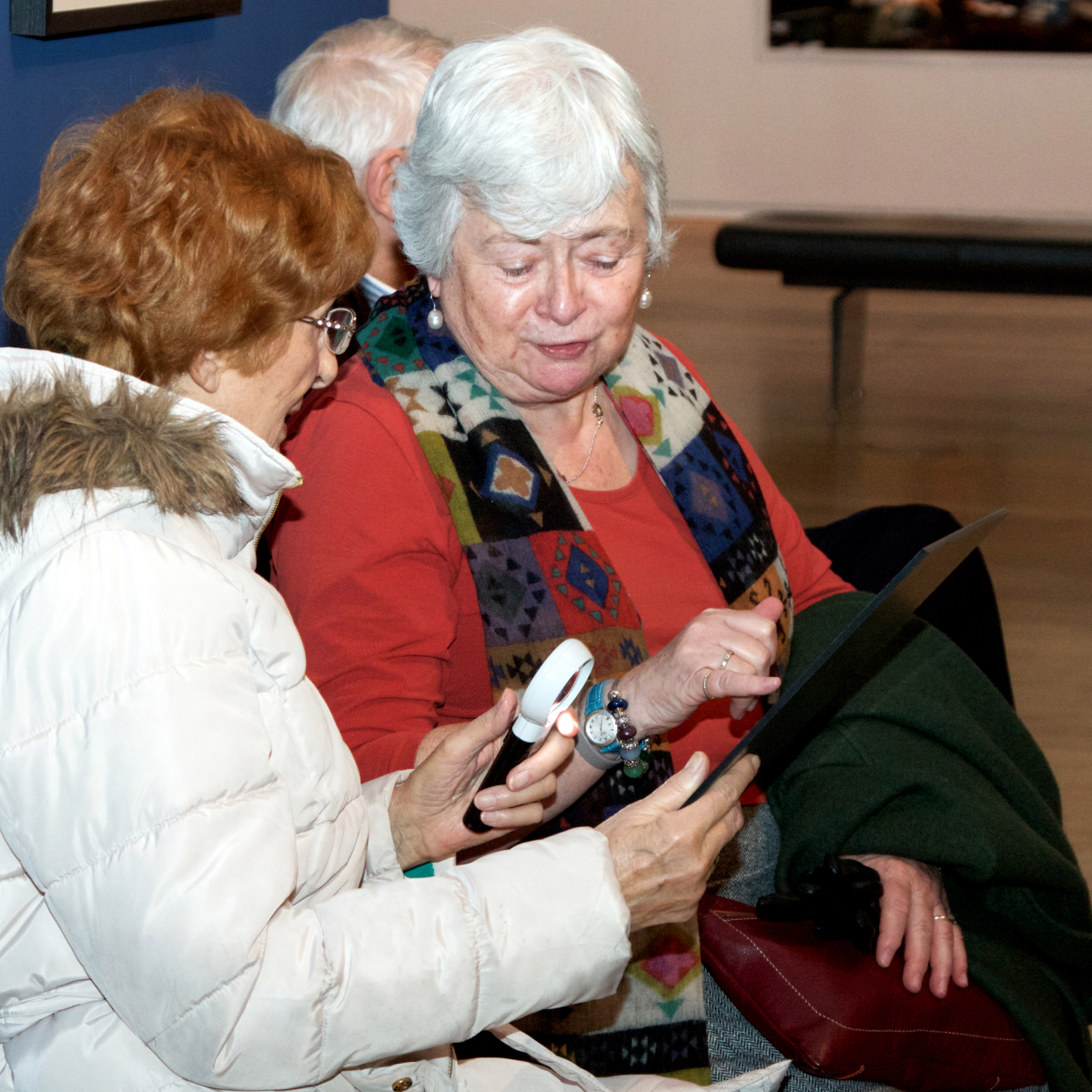 Two members of the Henshaws Group explore colour copies of artworks at a described tour of an exhibition at Gallery Oldham